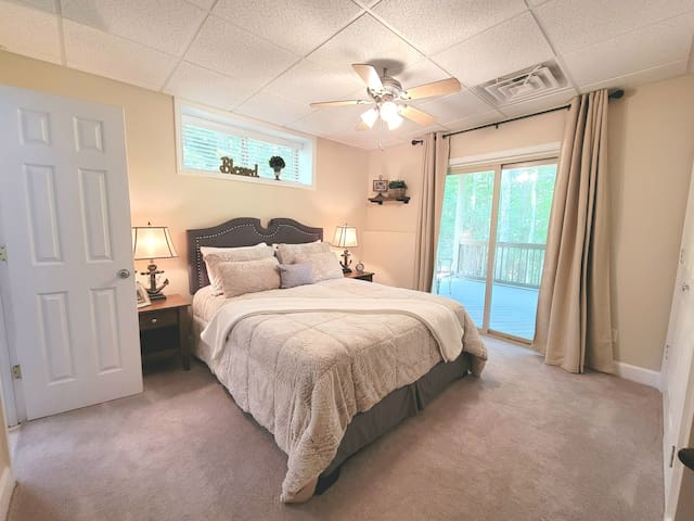 BR-4 Downstairs bedroom with ceiling fan, en-suite and sliders to outside patio deck.