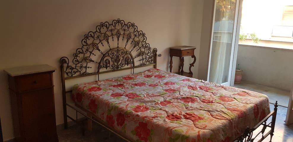 Ampia camera da letto matrimoniale con affaccio sul balcone, televisore, ventilatore, etc..