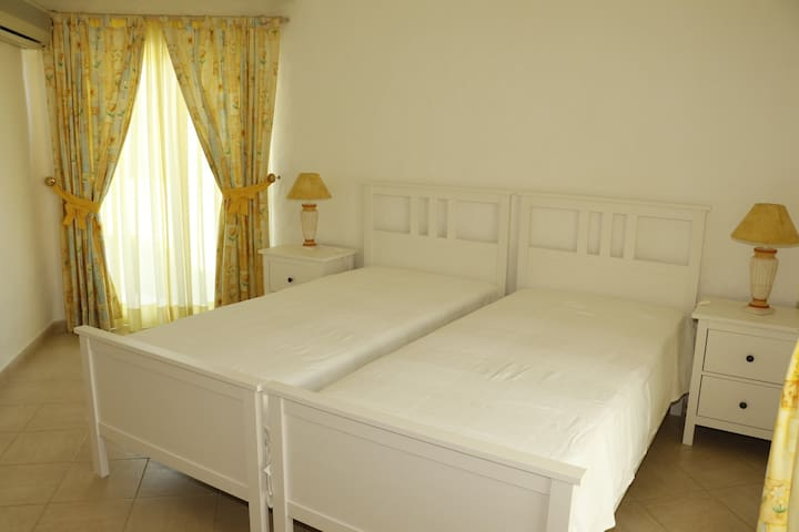 Bedroom suite on the ground floor with two single beds, spacious closet and direct access  to the garden and pool