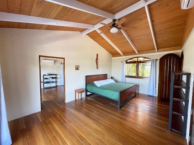 Bedroom 2,  equipped with air-conditioning, large windows and a fan.