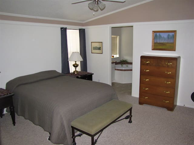 Master bedroom with a queen bed, and private bathroom with two sink vanities, a soaking tub, and a full sized shower.