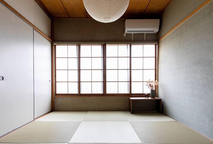 <Soothing Space to Rest>  磨りガラスの窓からやわらかな光が差し込む、二階の琉球畳の部屋。 静かにリラックスできる空間です。こちらにお布団を敷いて寝室としてもご利用いただけます。  Warm light in the Ryukyu-tatami room creates relaxing moments in the day and night.  Bask in the natural light filtering through the windows.