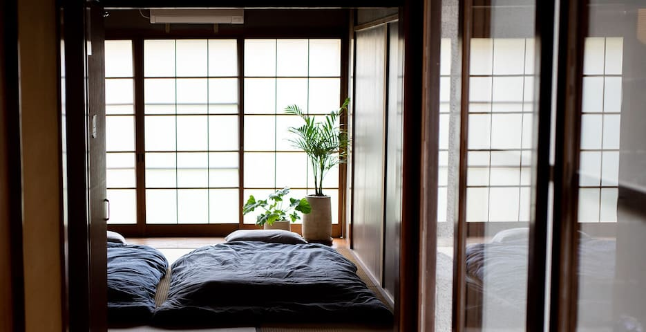 <Tea Room-Inspired Tatami Bedroom>  もともとは、客人をもてなす茶室だった一階和室。茶室だったころのおもかげの残る、明るく広々とした空間です。 夜はここにお布団を敷いて、リラックスできる寝室に早変わり。  Tatami flooring and decorations in the room create a warm and cozy atmosphere. This room is perfect for rest and relaxation.
