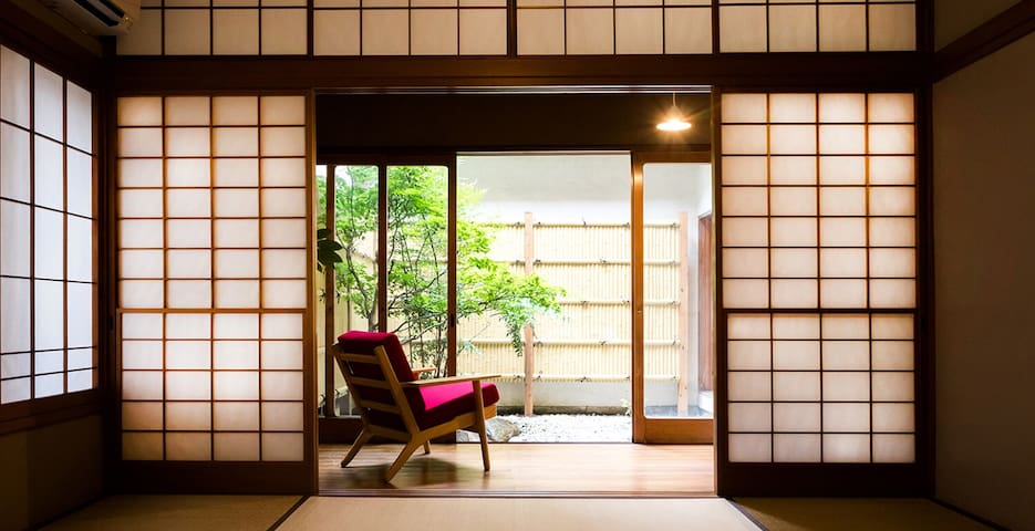 <Serene Lounge Space>  一階の坪庭がながめられる和室からの眺め。 広い縁側の赤いソファに座って日向ぼっこが気持ちいいスペースです。  Japanese living room with earthen walls and dark woodwork ceiling. The room opens up into the main hallway looking out onto the courtyard.