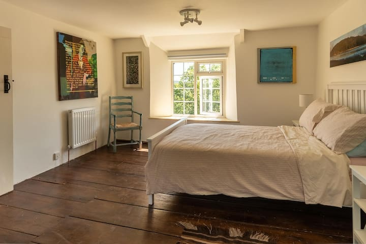 Original wide plank floor boards add to the simple beauty of this spacious double bedroom