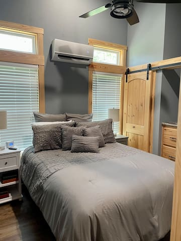 """The private Bedroom features a Queen-sized bed, built-in dresser and closet storage, remote controlled AC & Fan, and 32"""" Roku Smart TV."""
