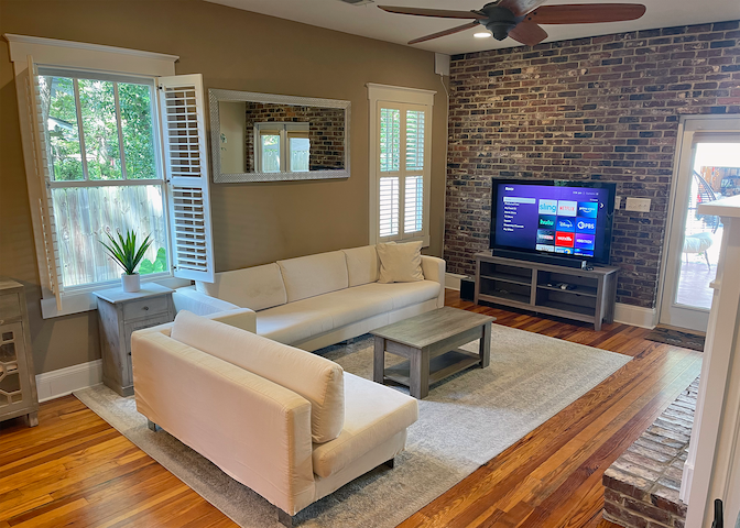 Living room area. Double doors to rear covered porch. Gas log fireplace. TV includes Sling cable TV, Netflix, Hulu and Disney+.
