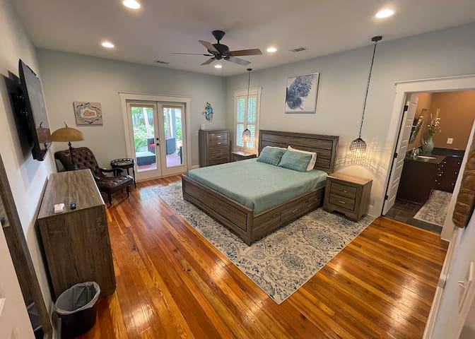 Main bedroom with California King bed. Private bathroom door on right. Double doors to rear covered patio on left.