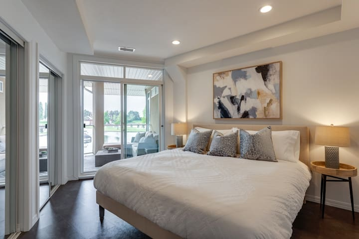 King bed master with water views, direct access to the patio, double closets and ensuite bathroom. Blackout curtains installed. Standing fan available.