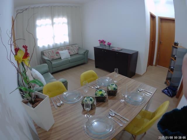 Sala com 2 sofás em couro, mesa, bufê e estante com livros.
