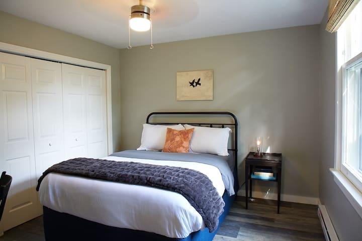 First floor Bedroom #1 with queen bed, desk and closet.
