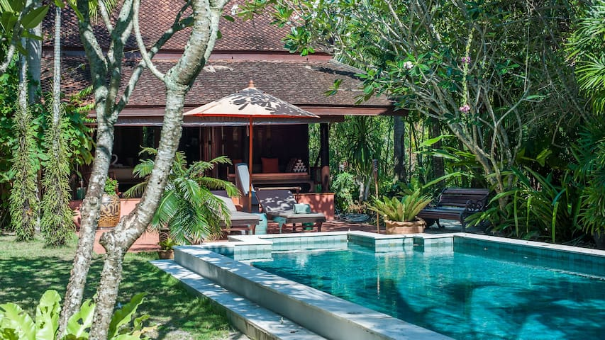 Private swimming pool surrounded by lush gardens