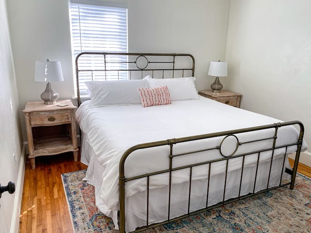 King bed with two night stands, two lamps, dresser, luggage rack and a closet.