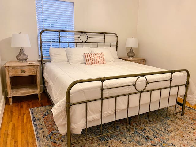 King bed with two night stands, two lamps, and a closet.