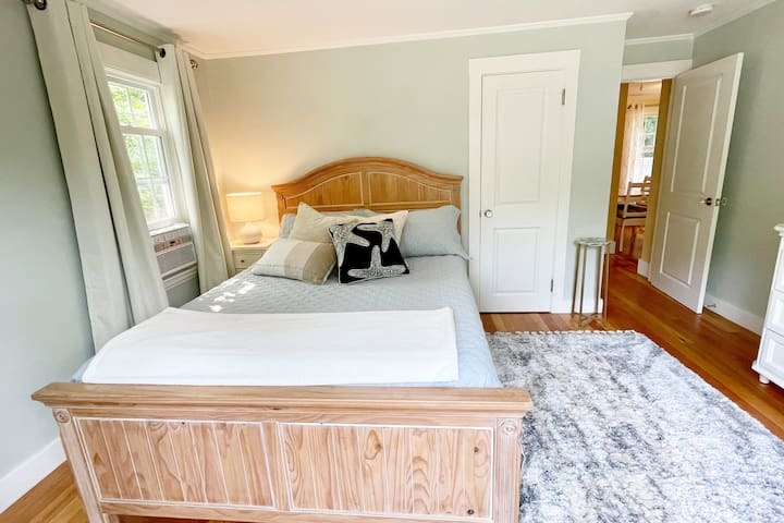 Bedroom number two. Full picture window with gorgeous morning sunlight. Queen size wooden bed with L.L. Bean's signature Pima Cotton Percale sheets. Full closet complete with luggage rack and hangers. A-C unit with remote control.