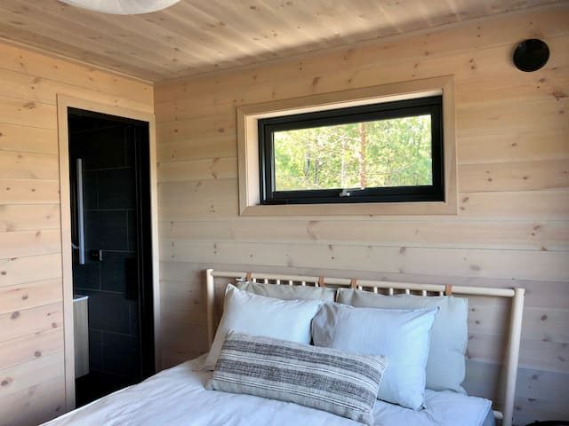 The master bedroom has separate entrance from the deck making it more private. It has an ensuite bath with a shower, a dresser for storing clothes, and hooks for hanging, and a queen-sized bed with views to the sea and stars.