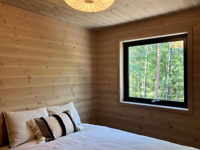 Bedroom #3 has a double bed with forest views, an ensuite bathroom with a shower,  under-bed drawers for storing clothes, and hooks for hanging.