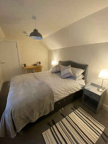 Main bedroom with king size bed, smart TV, desk, bedside tables & space to hang clothes