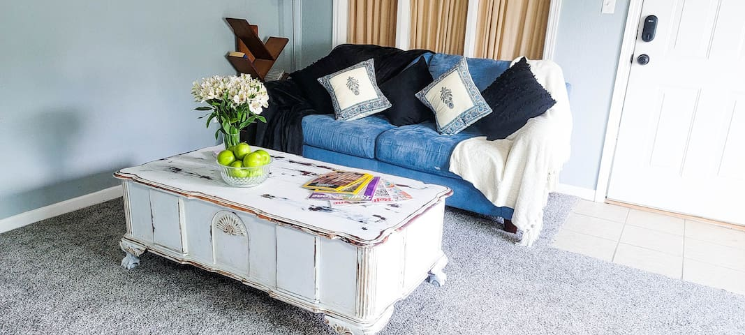 Nicely distressed vintage coffee table with tiger claw feet, and blue satin sofa with white and black sofa throws