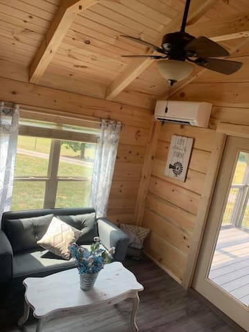 Sitting area - couch with fold down arms, ceiling fan and a/c unit
