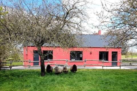 Petite maison rouge dans la campagne normande