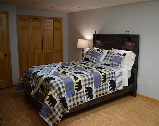 """DOWNSTAIRS BEDROOM Queen size bed, w/ nightstand, reading lights, set of bunk beds, (full & twin), closet with hangers, dresser for clothes, 55"""" Smart TV  and access to your private bathroom."""