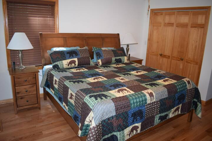 """MASTER BEDROOM King sleep number bed w/ remotes,  ceiling fan, nightstands, closet with hangers, dresser for clothes,  box fan, and 55"""" Smart TV."""