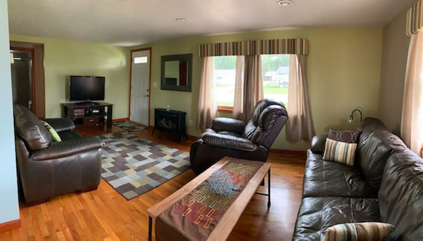 """Living room with leather couch, recliner and oversized chair. Gas fireplace. 42"""" TV with firestick (bring your Amazon acct info and de-register device before leaving) and DVD player"""