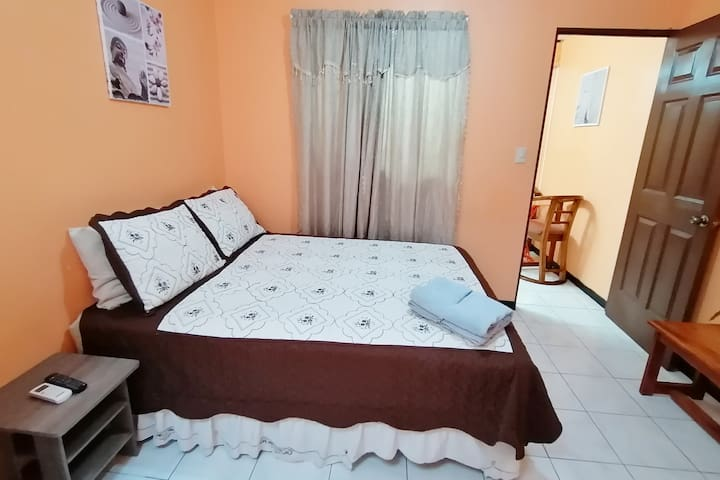 Queen size bed with cable tv, AC unit,  and private bathroom room.