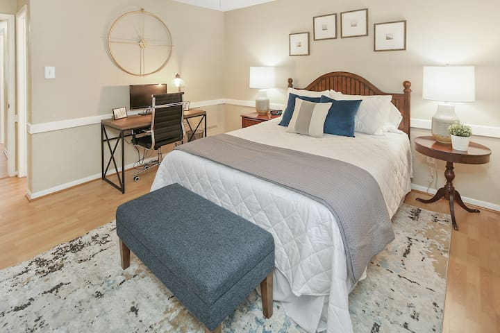 The master bedroom has a queen bed with a brand new, comfortable mattress.  This space includes a fully appointed desk with a monitor that can be used as a remote workspace.   It also has its own en suite bathroom.