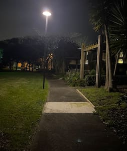 Entrance to terrace house down well lit reserve pathway