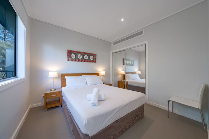The second bedroom features a queen-sized bed, topped with crisp white linens ready for you to sink into.