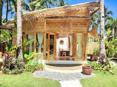 La casa de bambú · Jardín tropical y playa vacía