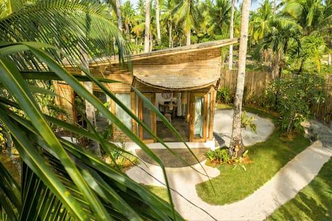 Het Bamboehuis · Tropische tuin en leeg strand