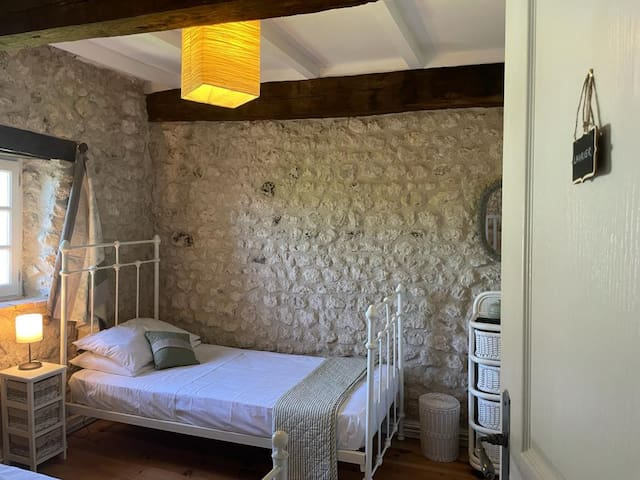 A twin bedroom perfect for best friends or little people with a shared bathroom.  Exposed natural stone walls add to the charm of this bijou room, with a picture window overlooking the rear grounds and swimming pool