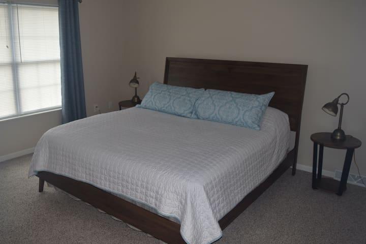 Master bedroom with king size bed, en-suite bathroom, and walk-in closet