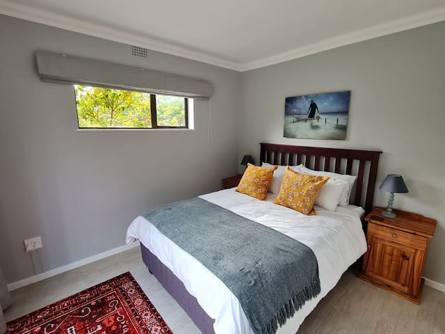 Downstairs bedroom No 1 with Queen Size bed, built-in cupboards and sliding door leading to the patio with beautiful mountain views and green garden to enjoy.