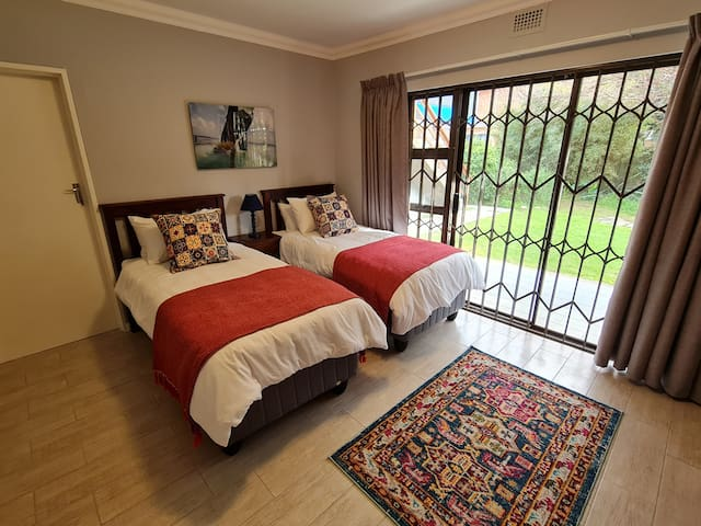 Downstairs bedroom No 3 with two single beds  and sliding door leading to patio with beautiful mountain views.