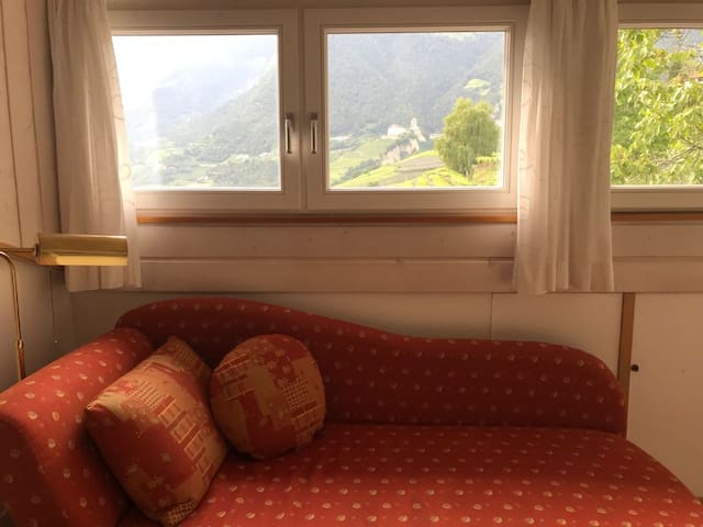 Ausziehcouch in der Wohnküche mit Blick auf Schloss Tirol. Divano-Letto nell Salotto-Cucina con Spettacolare Vista sull Castell Tirolo. Pull-out couch in the kitchen with an ammazing view on Tyrol Castle.