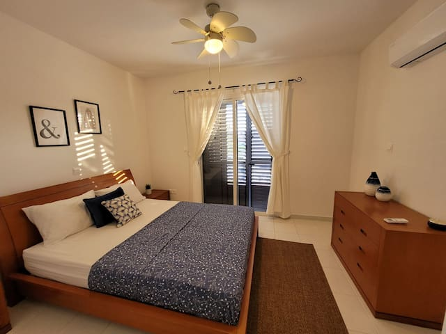 Master bedroom - with shutters, fly screens and curtains. Air conditioning. Almost 100% darkness at with shutters closed for a great night's sleep!