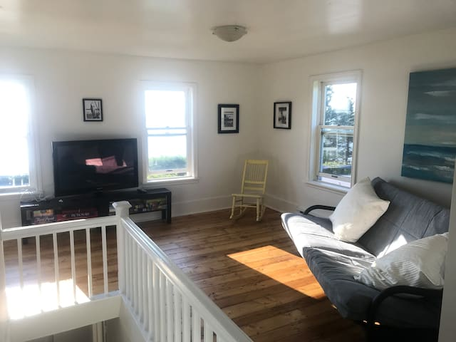 Upstairs living area with big screen and futon. HDMI cable provided so you can plug in your device for your favourite viewing.