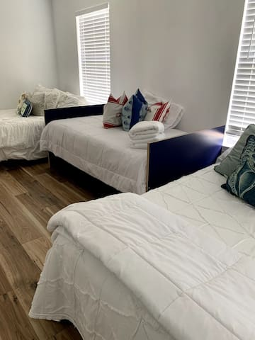 Large bedroom space with two double beds, and a twin trundle bed