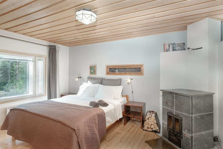 The cozy master bedroom with a luxuriously large king bed and a fireplace
