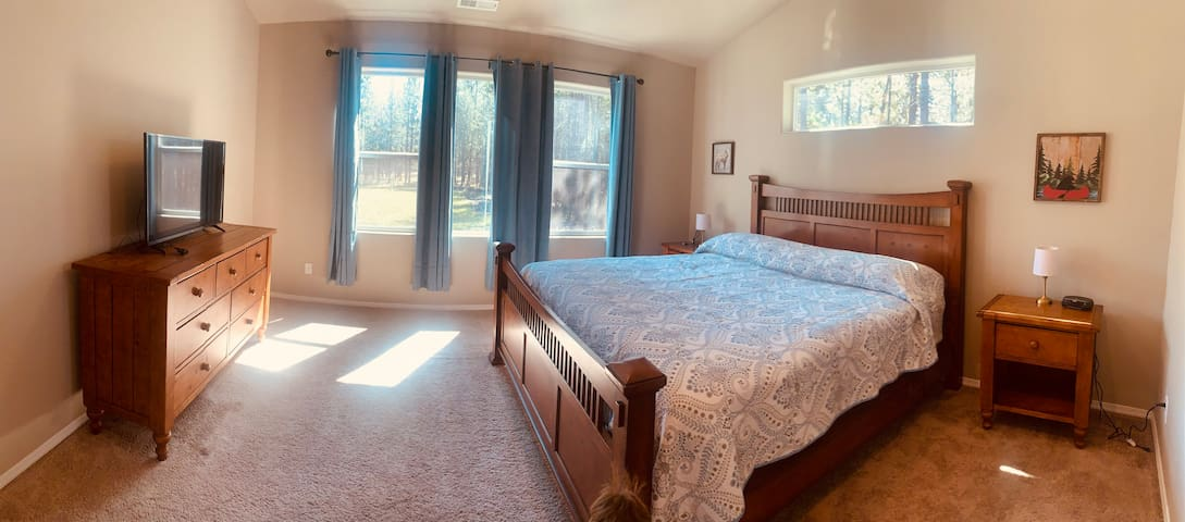 Large en suite master bedroom with panoramic window, television, and large windows letting in lots of light.