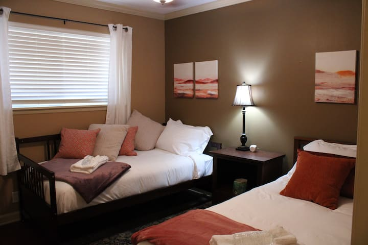 Room featuring two twin beds with full closet, nightstand, USB charging station, and ceiling fan.