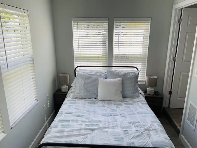 Guest bedroom equipped with full bed and television.