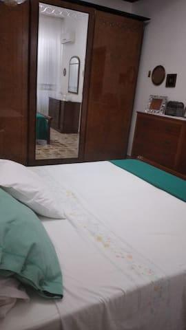 la camera da letto è stile classico, ampia tanto che può ospitare comodamente un lettino , con un luminoso balcone e climatizzata.