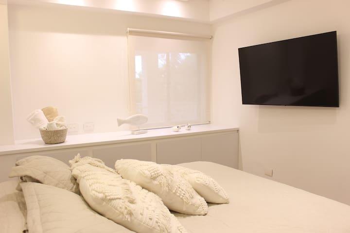 Hermosa habitación principal con TV pantalla plana y armario