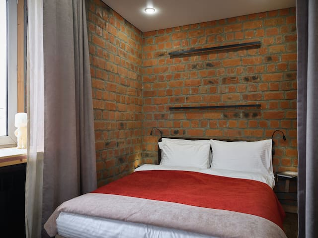 У кровати с каждой из сторон небольшие столики, ночные светильники и по 1 розетки. 4 подушки плотные (800 гр). Покрытие выполнено из специального материала тик.  2 одеяла на среднюю температуру (ни жарко ни холодно) выполнены из такого же материала.