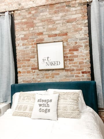 Master bedroom has exposed original brick, exposed floor joists, spiral ductwork, private balcony overlooking the Downtown Pocket Park,  private spa bath and walk-in closet.  Queen sized bed and wall mounted smart tv complete this heavenly space.